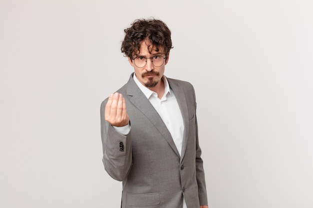 Young businessman making capice or money gesture, telling you to pay