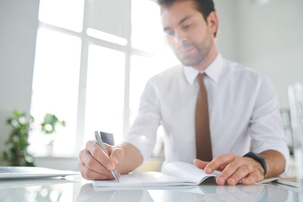 青年実業家のオフィスの机で彼の営業日を計画しながらメモを作る