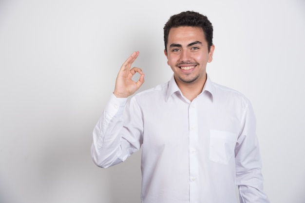 흰색 바탕에 한 손으로 확인 사인을 만드는 젊은 사업가.