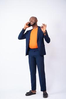 Giovane uomo d'affari che fa una telefonata con un gesto della mano ok isolato su uno sfondo bianco