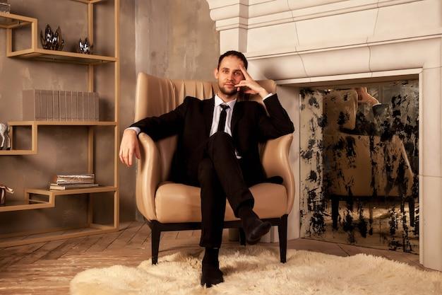 Молодой бизнесмен в костюме сидит на стуле в гостиной, взявшись за голову. жест человека указывает на спокойствие, расслабленность и домашний уют. понятие о человеческих эмоциях. копировать пространство