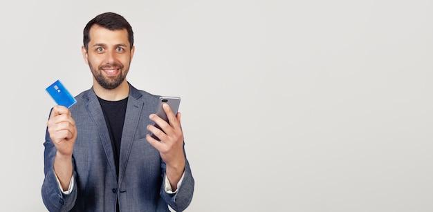 ジャケットにひげを生やした青年実業家、スマートフォンを使用してオンラインで支払うためにクレジットカードを使用してハンサムな男。