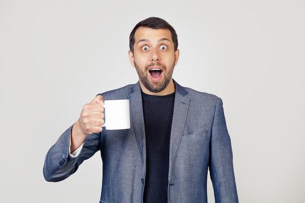 ジャケットにひげを生やし、一杯のコーヒーを持って、驚いた顔でショックで怖がり、恐怖の表現で怖がって興奮している青年実業家の男。