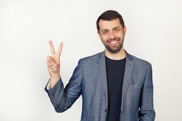 Молодой предприниматель человек с бородой в куртке, улыбаясь, глядя в камеру, показывает палец вверх, делая знак победы.