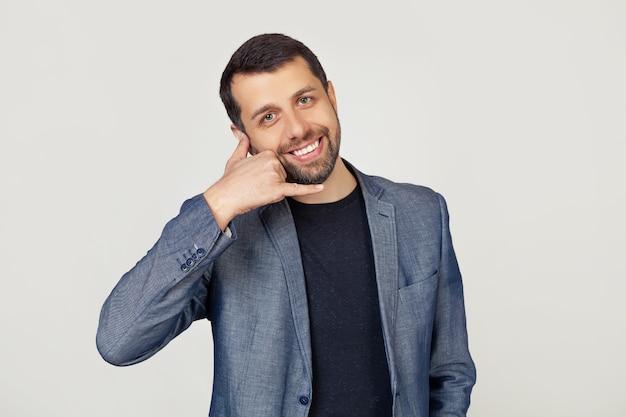 Молодой бизнесмен мужчина с бородой в куртке, улыбаясь, делая телефонный жест рукой и пальцами, как разговаривает по телефону.