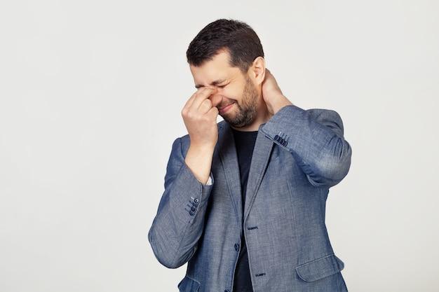 ジャケットにひげを生やした青年実業家、鼻と首をこするのにうんざりし、疲れと頭痛を感じています。