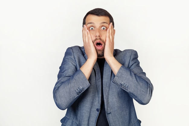 Молодой бизнесмен с бородой испугался и потрясен, удивлен и удивлен руками на его лице.