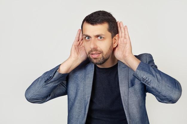 Молодой бизнесмен с бородой пытается услышать обе руки на ухе, любопытствуя о сплетнях.