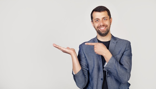 Young businessman man with a beard in a jacket, amazed and smiling, showing with his hand and pointing his finger.