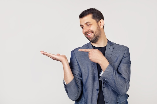 Young businessman man with a beard in a jacket looks at the palm, showing with his hand and pointing his finger.