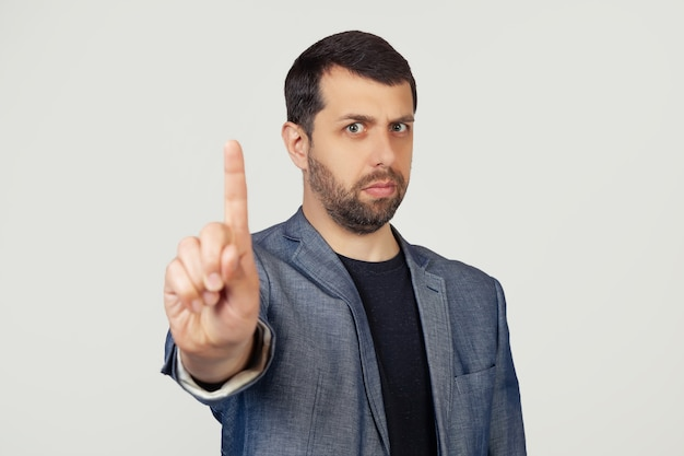 Young businessman man with a beard in a jacket pointing his finger up and angry expression without showing gestures.