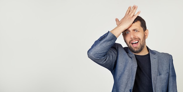 Young businessman man with a beard in a jacket, putting his hand on his head for a mistake feels stress, forced to cover up the mess or mistake.