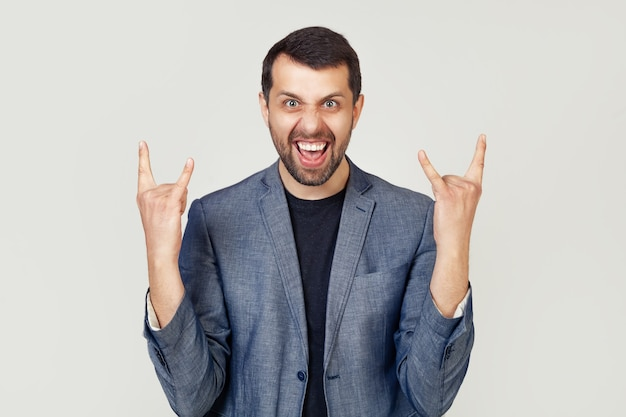 Young businessman man with a beard in a jacket, shouting with a crazy expression on his face, making a rock symbol with his hands up.