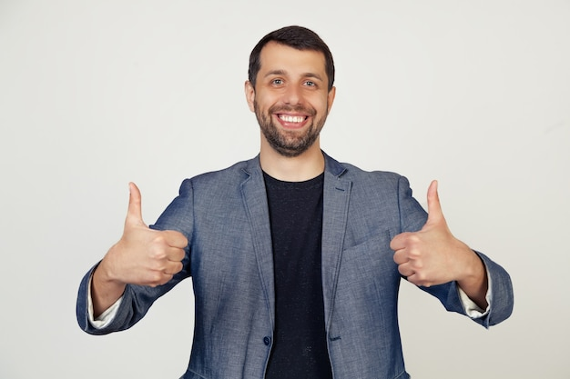 Young businessman man with a beard in a jacket, a sign of success makes a positive gesture with his hand, thumbs up smiling and happy.