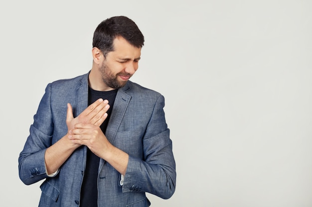 Young businessman man with a beard in a jacket, suffering from pain in the hands and fingers, inflammation of arthritis.