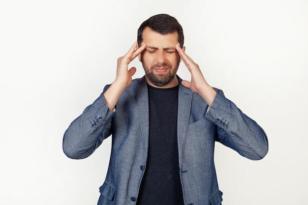 ストレスによる頭痛の手でひげを生やした青年実業家。片頭痛に苦しんでいます。