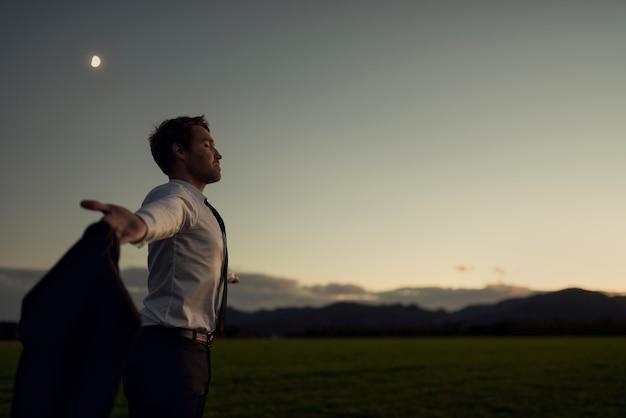 Молодой бизнесмен медитирует на природе, стоя с распростертыми объятиями, держа куртку в поле, когда солнце встает над горами в новый день.