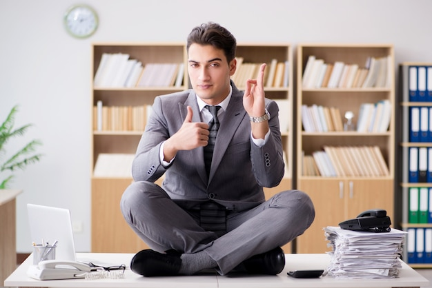 Young businessman meditating in the office
