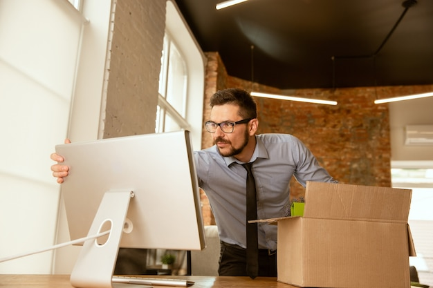 A young businessman moving in the office, getting new work place. young caucasian male office worker equips new cabinet after promotion. looks happy. business, lifestyle, new life concept.