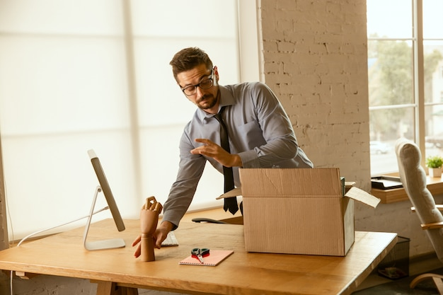 A young businessman moving in the office, getting new work place. young caucasian male office worker equips new cabinet after promotion. looks happy