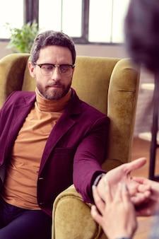 Молодой бизнесмен. хороший серьезный мужчина смотрит на свою руку во время посещения хироманта