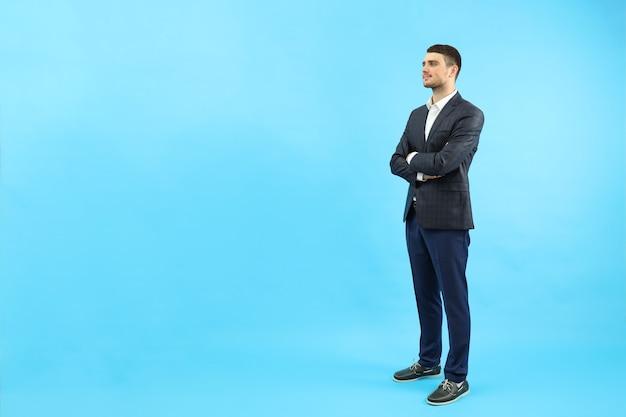 Молодой бизнесмен на синем фоне, место для текста.