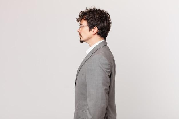 Молодой бизнесмен на взгляде профиля мышления, воображения или мечтания