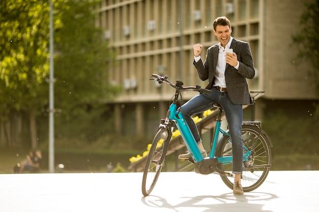 自転車に乗った青年実業家が携帯電話で悲報を受け取った