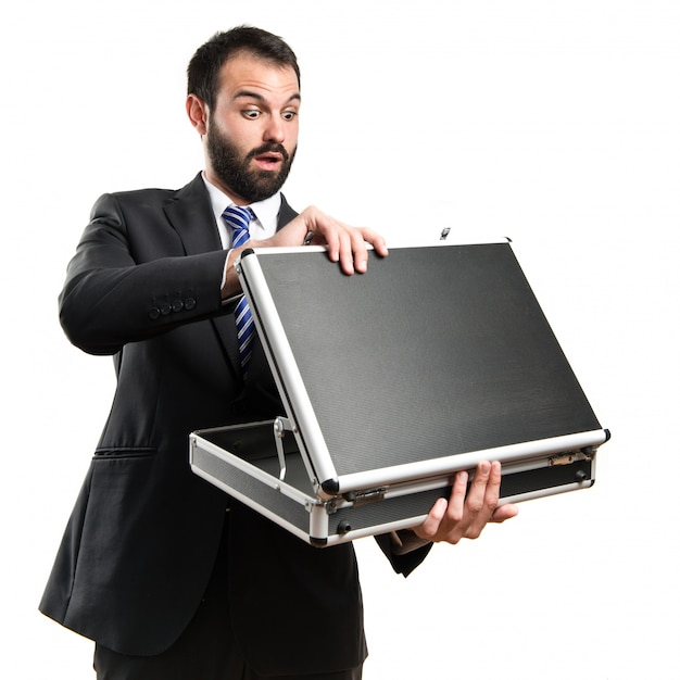 Young businessman opens his briefcase over white background