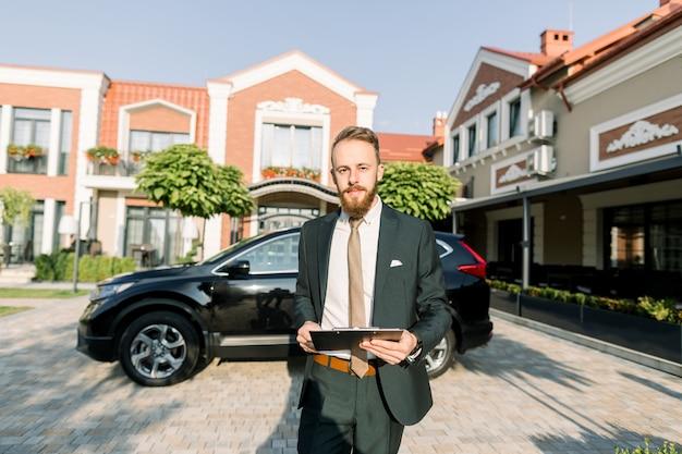 Молодой бизнесмен или менеджер по продажам в темном костюме стоял на открытом воздухе во дворе бизнес-центра с новым черным автомобилем