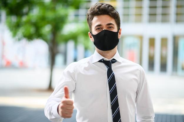 現代的な設定で屋外の青年実業家は親指をあきらめ、covid19コロナウイルスパンデミックに対する保護マスクを着用します