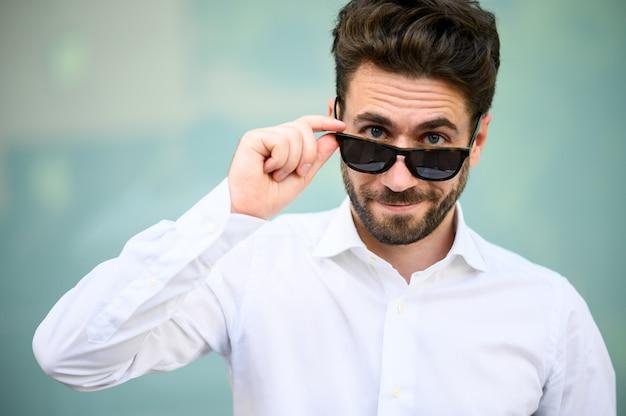 彼のサングラスを保持しているモダンな設定で屋外の青年実業家
