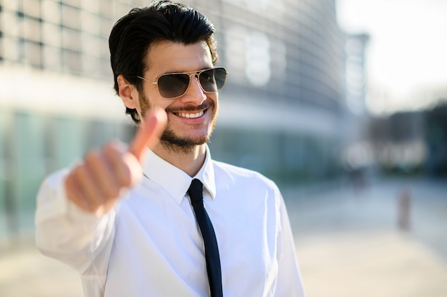 サングラスをかけ、親指をあきらめる屋外の青年実業家