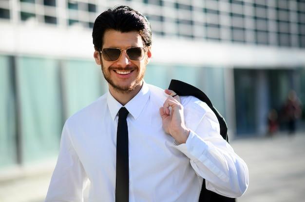 サングラスをかけ、晴れた日に彼のジャケットを保持している屋外の青年実業家