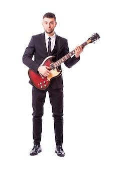 Молодой бизнесмен играет на гитаре, изолированные на белой стене