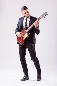 Giovane imprenditore a suonare la chitarra isolata sul muro bianco