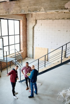 작업 회의에서 동료와 벽돌 또는 패널의 품질을 논의하는 동안 미완성 건물의 벽을 가리키는 젊은 사업가