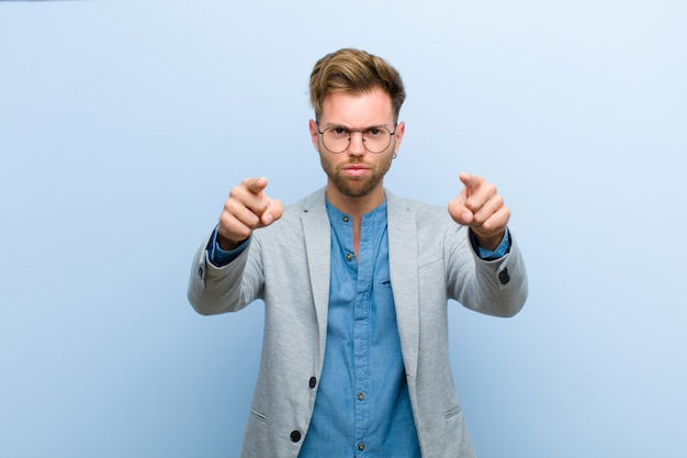 Young businessman pointing forward at camera with both fingers and angry expression, telling you to do your duty against blue