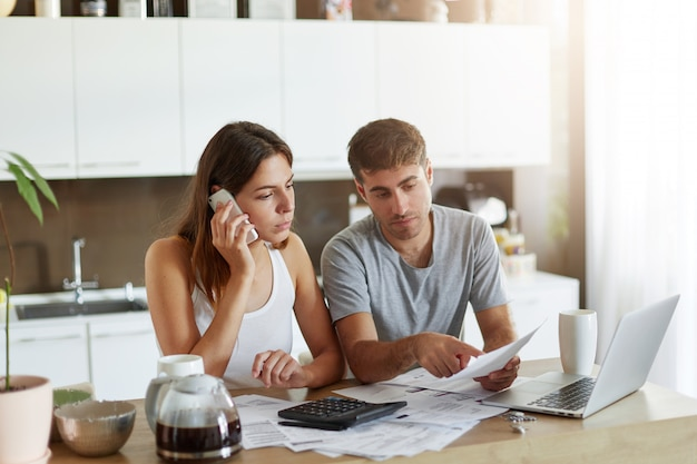 Young businessman pointing with finger at document, trying to expain something to his wife who is speaking over smart phone. couple reviewing their bank accounts and calculating annual figures