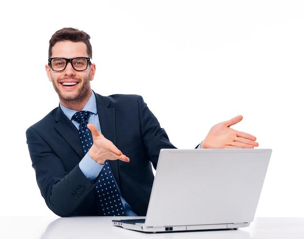 若いビジネスマンはコンピューターを指しています