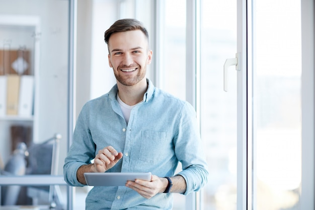 Young businessman posing by window