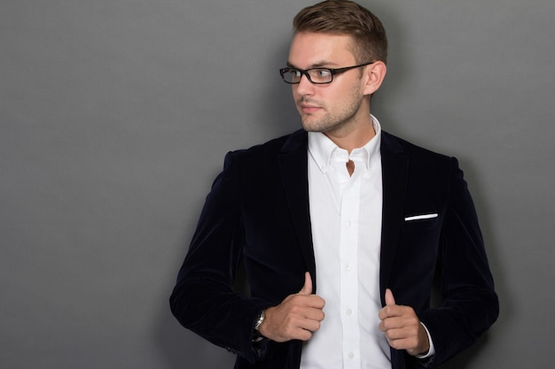 Young businessman posing chic in work suit and glasses