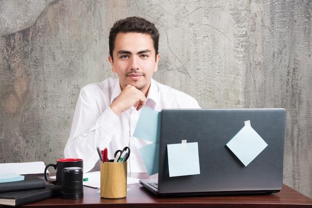 Молодой бизнесмен, счастливо позирует за офисным столом.