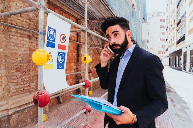Young businessman posing with phone and folder