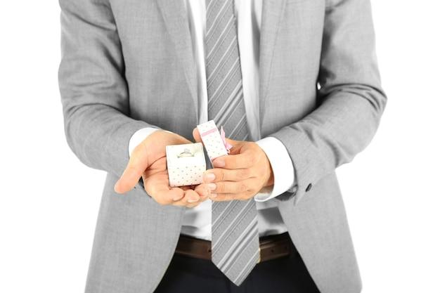 Молодой бизнесмен представляет подарочную коробку с кольцом, изолированным на белом