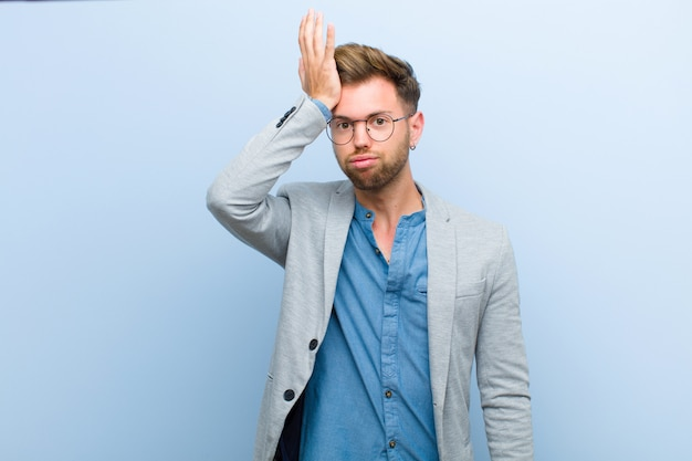 Young businessman raising palm to forehead thinking oops, after making a stupid mistake or remembering, feeling dumb