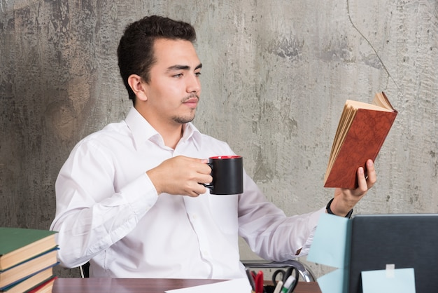 Giovane imprenditore leggendo un libro e bevendo il suo tè alla scrivania.