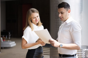 Young businessman reading document to smiling businesswoman