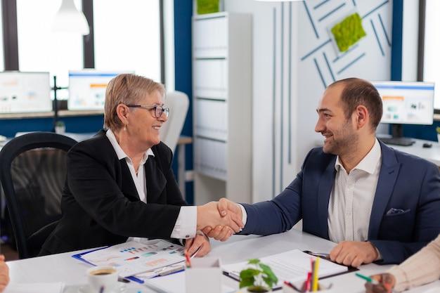 젊은 사업가 문서를 읽고, 파트너십 거래를 계획 한 후 악수와 함께 국제 고객을 인사하는 컨설턴트에 서명합니다. 스타트 업 오피스에서 주주 총회 상무 이사
