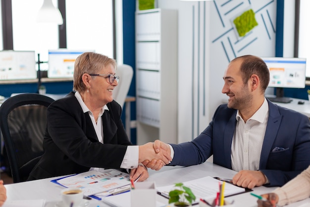 Young businessman reading documents, sign its and consultant greeting international client with handshake after planning partnership deal. executive director meeting shareholders in start up office